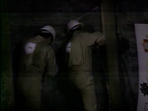 Workmen drill through the final section of the Channel Tunnel 1990