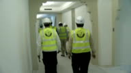 Construction sites with building inspectors EXT Construction workers or site inspectors standing on roadside or car park area near to construction...
