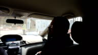 Construction sites with building inspectors INT inside car filmed from back passengers seat showing unidentified man in front passenger seat giving...