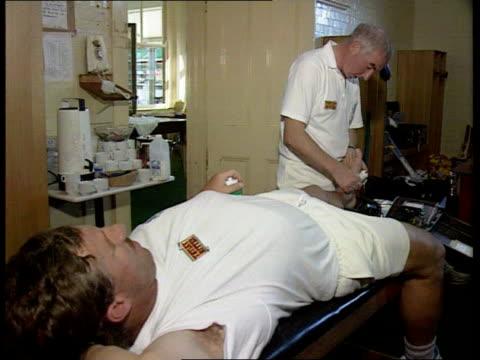 England team AUSTRALIA Sydney MS England physiotherapist Laurie Brown treating Ian Botham as Derek Pringle looks on CMS Brown BV Brown working on...