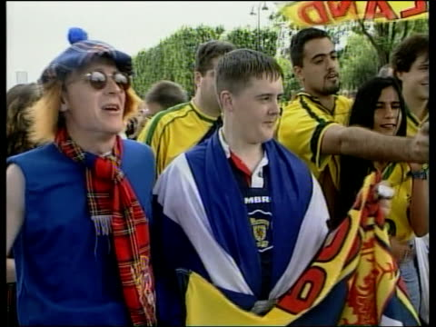 Scottish fans in Paris MS Bare chested Scotland fans with painted faces tartan hats holding bottles of beer with arms about each other Vox pops...