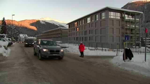 David Cameron negotiating EU reform in Davos EXT Cars along ice and snowcovered road Sun shining on snowcovered mountain
