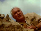 World renowned archaeologist anthropologist Dr Louis Leakey working behind rock at Olduvai Gorge / Dr Louis Leakey examing and discussing human...
