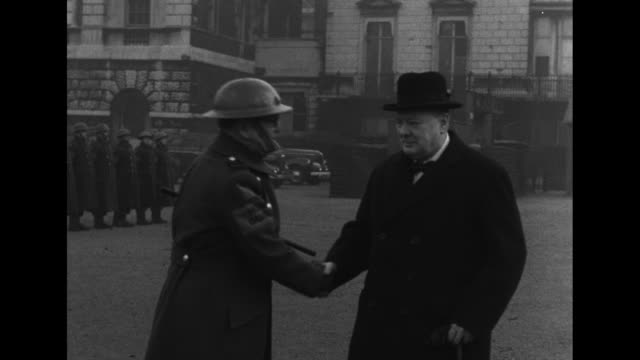 World War II / CU British Home Guard volunteers / Winston Churchill walking to Brig General Wade Hampton Hayes and shaking hands / CU Hayes / CU...