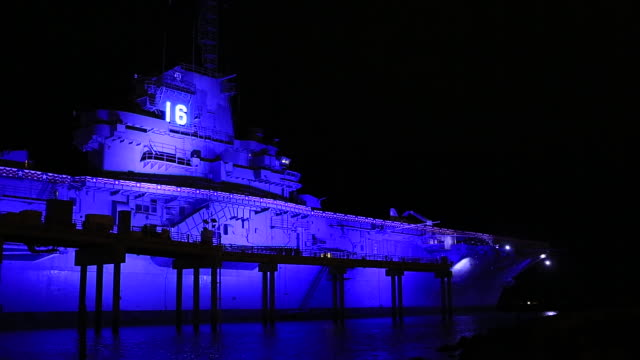 WS World War II era USS Lexington Essex Class aircraft carrier covered in blue light docked at pier dark sky BG National Historic Landmark
