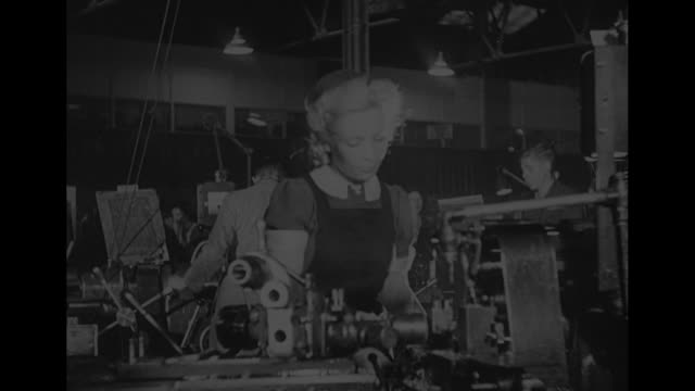 World War II / interiors Avro Lancaster airplane factory / factory workers manufacturing plane parts / CU woman operating machine / CU man operating...