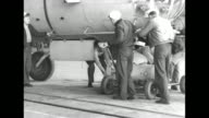 World War II / US Navy sailors leaning against a blimp / sailors arrive at blimp with bombs on dolly / bombs loaded onto blimp / blimp on tarmac /...