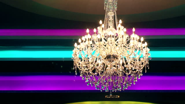 Worm Eye View of Crystal Gold Chandelier with Multi-Colored Background.