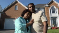 Worried Couple in Front of Home