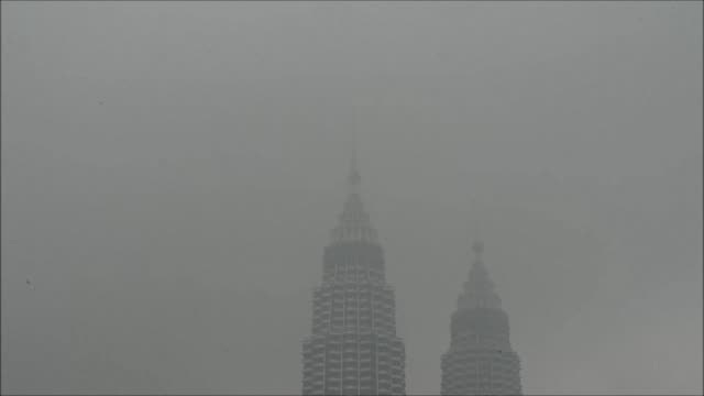 Worsening haze from Indonesian forest and agricultural fires envelop Kuala Lumpur in a smoky grey shroud forcing the closure of schools in Malaysia...