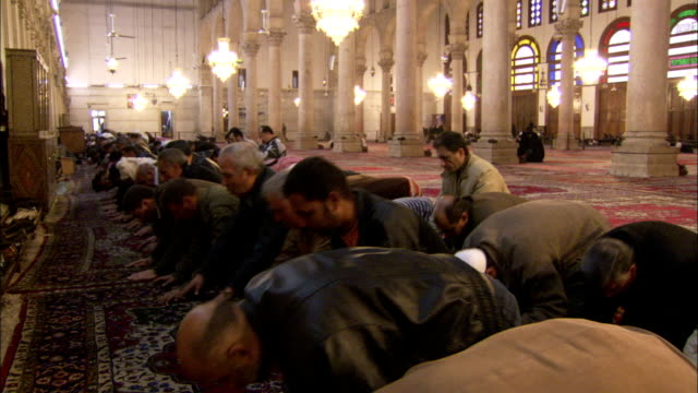 Worshipers kneel and bow in prayer in the Umayyad Mosque Damascus. Available in HD.