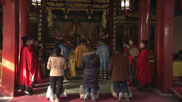 Worshipers kneel at an altar while priests chant and play instruments in the Bai Yun Guan Temple in Beijing.