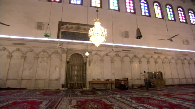 Worshipers walk around the main room of the Umayyad Mosque Damascus. Available in HD.