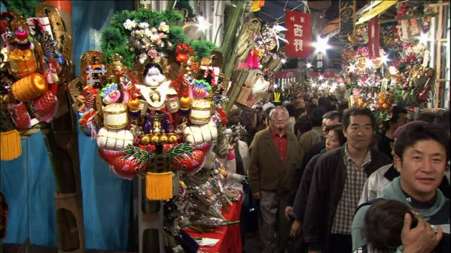 Worshippers carry lucky rakes through the Ohtori Shrine market.  Tori-no-Ichi