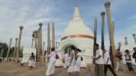 MS Worshippers passing Thuparama Dagoba, the first dagaba built in Sri Lanka after introduction of Buddhism, contains collarbone of Buddha / Anuradhapura, North Central Province, Sri Lanka