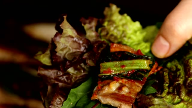 Wrapping pork belley in lettuce leaves with Gat (leaf mustard) Kimchi (Popular traditional side dish in Korea) and garlic
