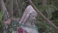A wreath of flowers hangs around the neck of a statue of the Virgin Mary in a garden.