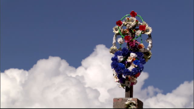 Wreaths decorate a cross. Available in HD.