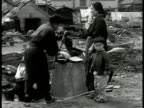 Wrecked building Japanese workers digging FG WS Japanese women pumping water child destroyed village BG WS Trolley passing on street bombed building...