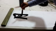 Writing calligraphy with brush on paper
