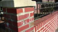Wrought iron railings decorate brick columns.