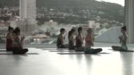WS_Big yoga class meditating, in rooftop studio