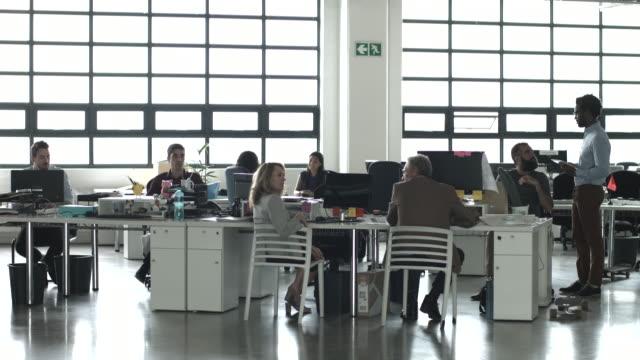 WS_Creative businesspeople talking in big open office