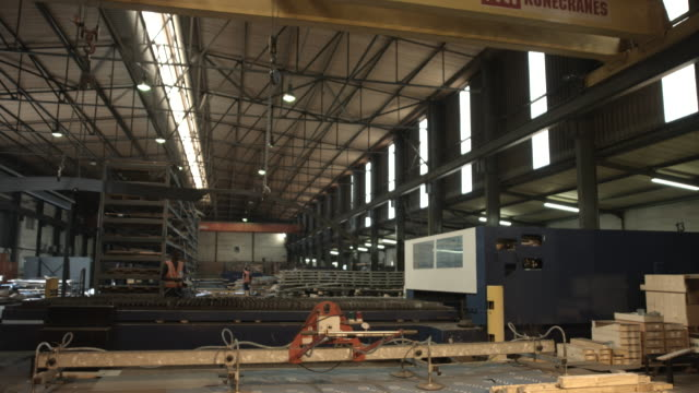 WS_Worker at steel factory operating lift and moving steel sheet