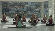 WS_Yoga teacher explains breathing techniques to students, in rooftop studio