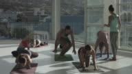 WS_Yoga teacher instructing students in handstand, in rooftop studio