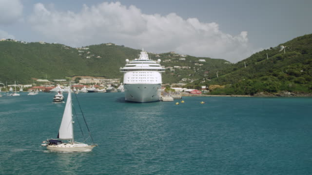 WS AERIAL POV Yacht moving in bay, cruise ship moored in background / Charlotte Amalie, Saint Thomas, US Virgin Islands, United States