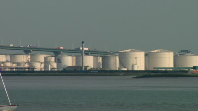 MS, yacht passing by fuel storage tanks on river Thames / Kent, England