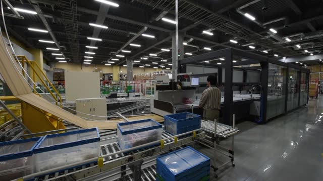 Yamato Logistics Co employees demonstrate the Neopost SA CVP500 automated packing system at the Yamato Holdings Co Atsugi Gateway distribution center...