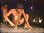A Yanomami Indian man sharpens a knife inside a traditional Maloca dwelling in the Amazon