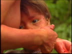 A Yanomami Indian mother applies facepaint to her child in the Amazon
