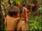 Yanomami Indians carry children through the Amazon rainforest