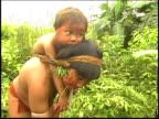 Yanomami Indians picking herbs with children