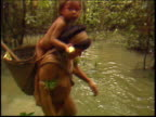 Yanomami Indians walking through shallow water in the Amazon rainforest