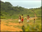 Yanomamo Indians flee from a plane approaching a jungle runway by a gold mine