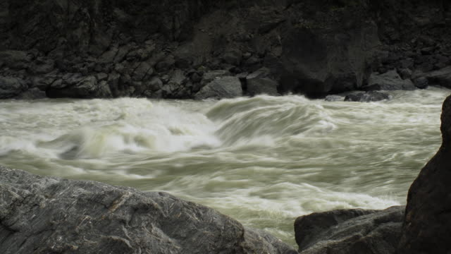 Yarlung Tsangpo river splashes over rocks, Tibet, China