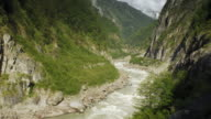 Yarlung Tsangpo river winds through lush valley with mountains beyond, Tibet, China