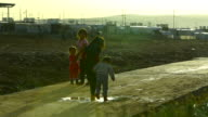 Yazidi children walk home at sunset inside a refugee camp in northern Iraq Approximately 20000 people live inside the Khanke refugee camp in northern...