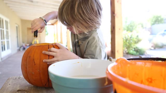 4 year old boy carving a pumpkin