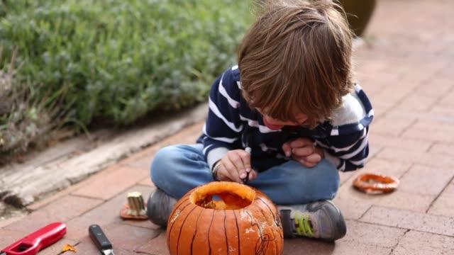 4 year old boy drawing on pumpkin