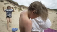 A 10 year old boy drying his hair on the beach.