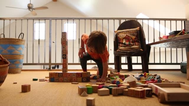 4 year old boy playing with wooden blocks