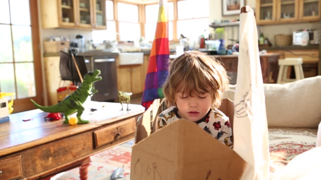 4 year old boy sitting in cardboard ship on couch