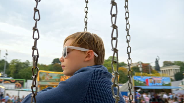 10 year old boy takes a chain swing carousel ride while visiting the 'Oide Wiesn' during Oktoberfest 2017 - thoughtful child with white sunglasses