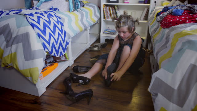 8 year old boy tries on some high heels to go with his shiny blue dress