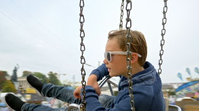 10 year old boy wearing sunglasses takes a chain swing carousel ride while visiting the 'Oide Wiesn' during Oktoberfest 2017 - blurred background